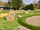 Bahnen des Abenteuer Golfparks abgetrennt durch Steine und Holzblöcke
