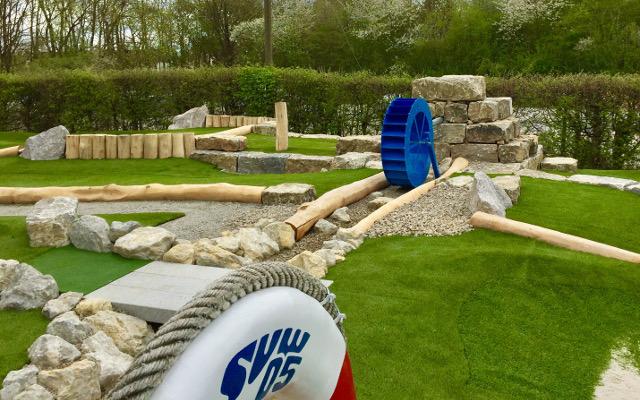 Blick über den Rettungsring auf das Wasserrad der Abenteuer Golfpark-Anlage